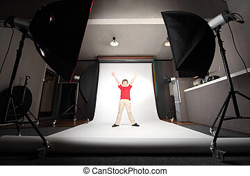 interior of professional photo studio boy in red shirt standing on white background