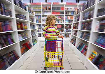 Little girl in bookshop, with cart for goods. There is one...