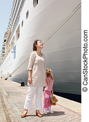 young mother and daughter standing in dock near big cruise liner and looking on it