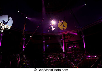 circus performance with two trapeze gymnasts purple light