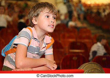 little boy in circus leans on red rail looking into the...