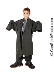 little boy in big grey man's suit and boots stabding...