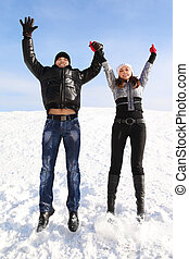 young man and girl jump on snowy area and smiling, holding for hands, looking at camera