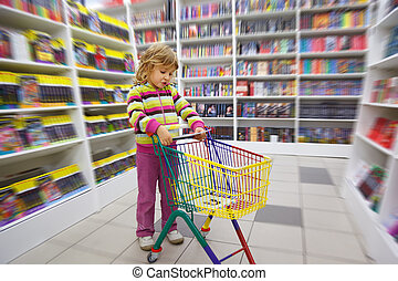 Little girl in bookshop, with cart for purchases. Disapprovingly looks at book at itself in hands.