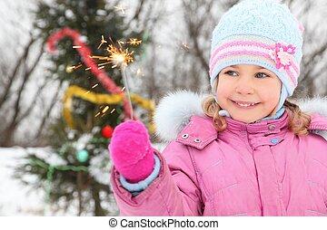 little girl wearing winter jacket is standing near...