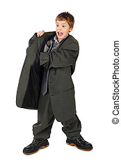 little boy in big grey man's suit and boots hand in pocket isolated on white background