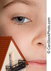face of little girl near toy plastic house with balcony