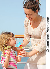 mother and daughter standing on cruise liner deck, mother holding cocktail in glass, daughter drinking it, vertical