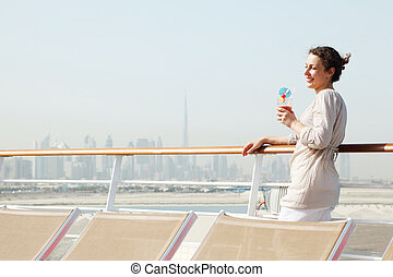 young beauty woman with cocktail standing on cruise liner deck, half body