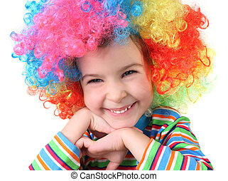 little girl in clown wig smiling and looking at camera, chin on hands, half body, isolated