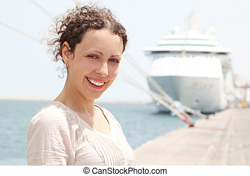beauty brunette woman smiling and looking at camera, big cruise liner on background