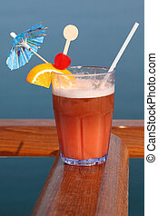 cocktail with fruits in glass on ship deck rail, sea on background, vertical