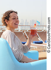 beauty woman sitting in blue armchair on cruise liner deck and holding cocktail in glass, cityscape on background