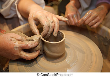 Hands of master creating pot on potter's wheel. Traditional...