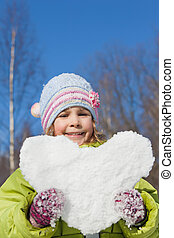 smiling little girl keeps in hands hearts from snow in...