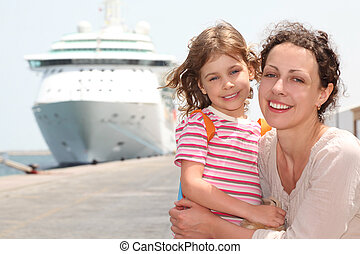 mother and daughter embracing, smiling and looking at...