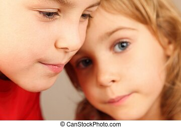 faces of two children. focus on little boy's eye. little girl's face in out of focus.
