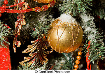 Christmas toy in form of sphere hanging on artificial fur-tree, sphere in snow