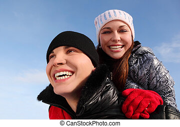 young girl embracing man from back, smiling and looking at camera, sky on background