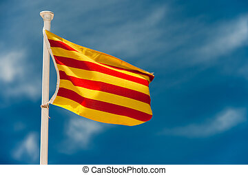 Catalan flag blowing in the wind with blue sky