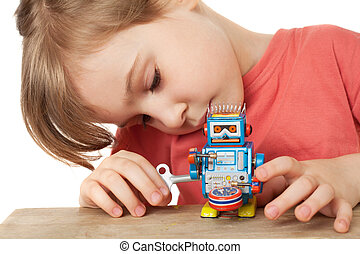 little girl in red T-shirt plays with clockwork robot...