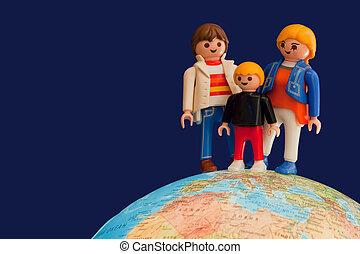 Toy parents and child standing on globe is illuminated from withinon dark blue background