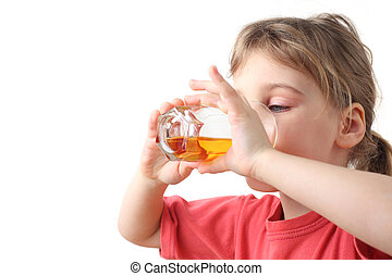 little girl in red shirt holding glass with juice for two hands and drinking it, half body
