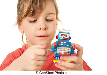 pretty little girl in red T-shirt plays with clockwork robot...