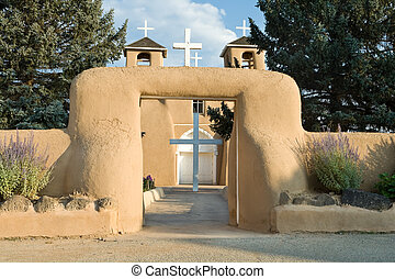 Main church entrance with surrounding adobe wall. Crosses on...