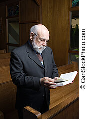 Standing Senior Caucasian Man Reading Hymnal In Church Pew -...