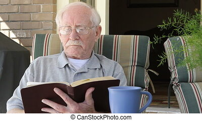 Senior Reads Bible - Elderly man sits in an outdoor chair...