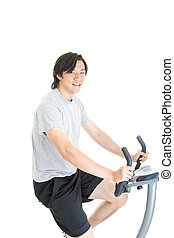 Asian man on a stationary bike in work out clothing.  Isolated on white background.