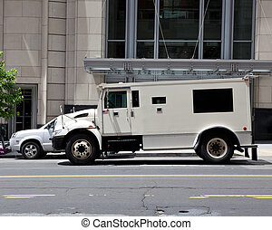 Side view of gray armored double parked on street making a...