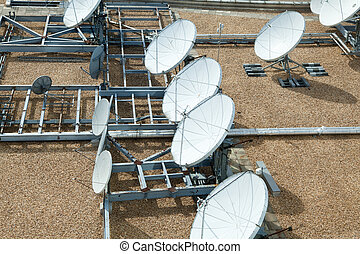 Collection of Large Satellite Dishes on Flat Gravel Roof