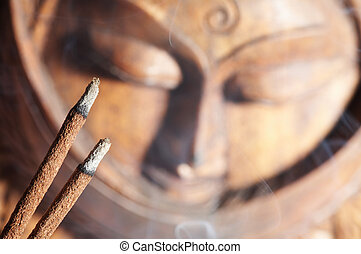 Smoldered sandal-wood incense and Buddha image background