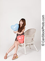 Happy smiling lady holding heart shaped balloon and sitting...