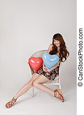 Cheerful smiling lady holding heart shaped balloon and...