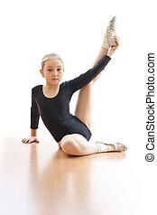 Girl making exercises on floor in bodysuit