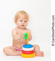 Baby girl playing with colorful pyramid