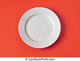 White round plate on red background