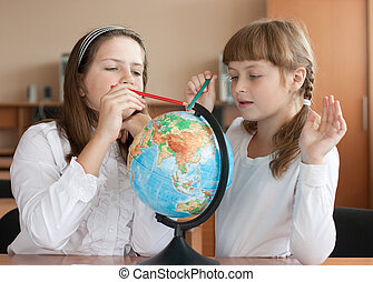 Two schoolgirls search geographical location using globe