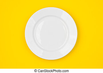 White round plate on yellow background