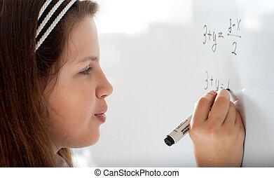 Cute preteen schoolgirl writing letter on whiteboard...