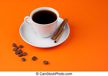Black coffee cup on orange with cinnamon and beans