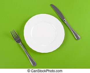 Knife, white round plate and fork on green background -...