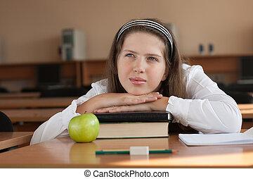 Schoolgirl's portrait at school desk with her books -...