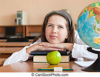 Schoolgirls portrait at school desk with her books and globe...