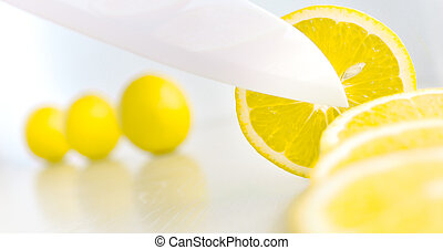 White ceramic knife cutting lemon