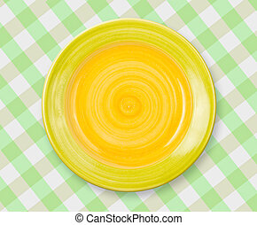 Round yellow plate on checked tablecloth