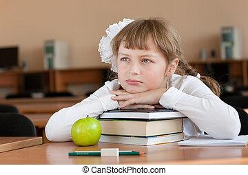 Schoolgirl's portrait at school desk with her books
